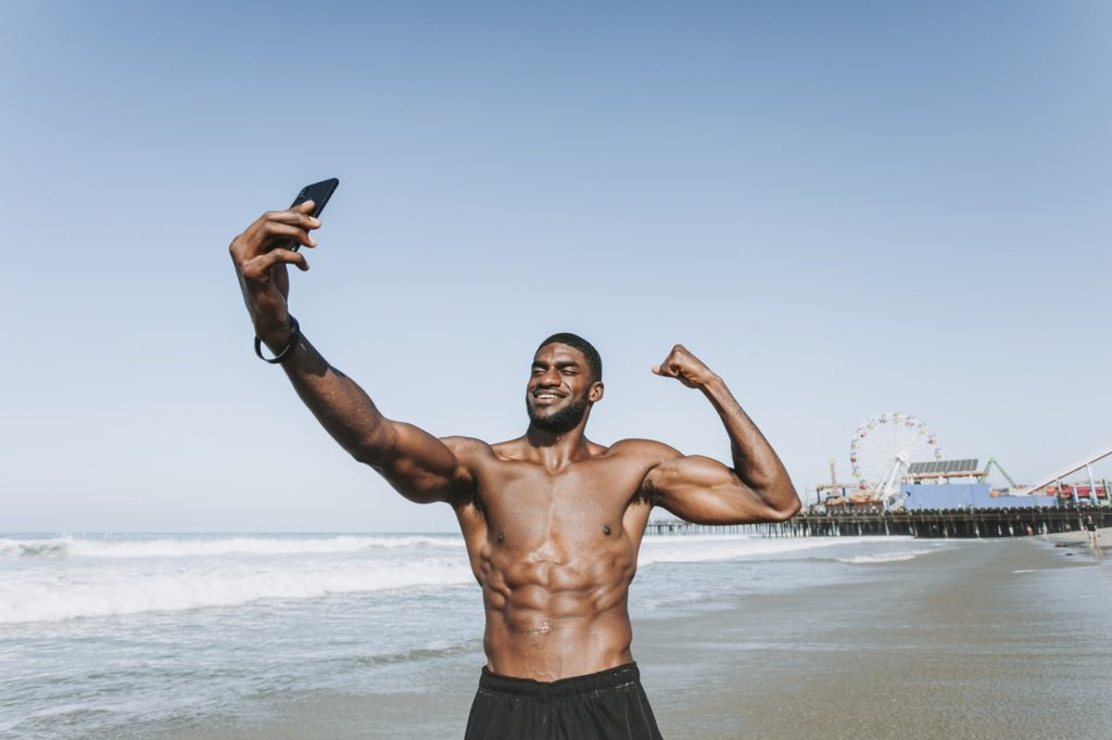 Man taking a selfie and flaunting his body at the beach